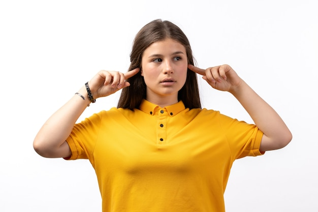 Mulher de camisa amarela e calça jeans posando e colando as orelhas nas roupas de modelo de mulher de fundo branco