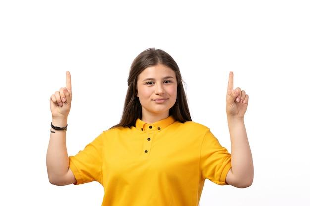 Mulher de camisa amarela e jeans azul posando com os dedos levantados nas roupas de modelo de mulher de fundo branco