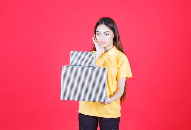 Mulher de camisa amarela segurando grandes e pequenas caixas de presente de prata e parece pensativa.