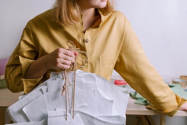 Mulher de camisa amarela segurando padrões de vestido de papel em sua oficina