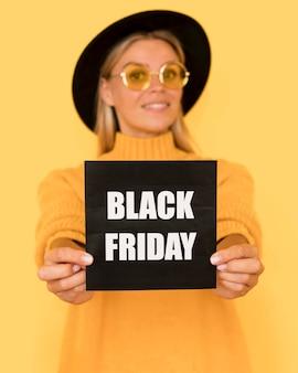 Mulher de camisa amarela segurando um cartão quadrado preto de sexta-feira