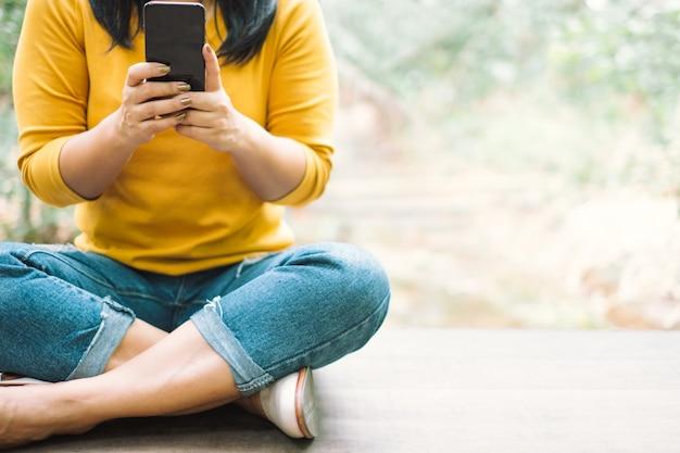 Mulher de camisa amarela, segurando um telefone móvel preto