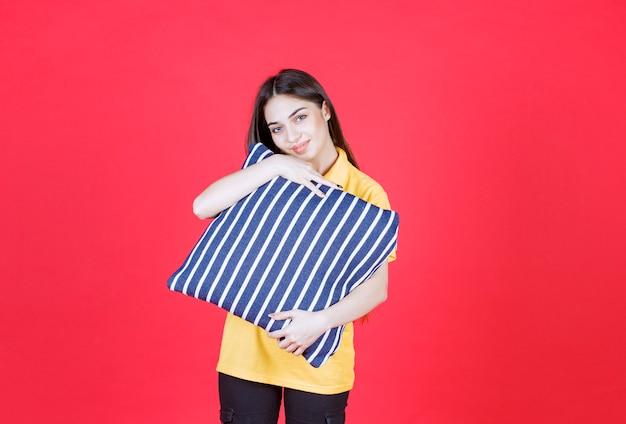 Mulher de camisa amarela segurando um travesseiro azul com listras brancas e parece pensativa.