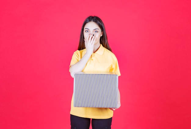 Mulher de camisa amarela segurando uma caixa de presente prata e parece confusa e pensativa.