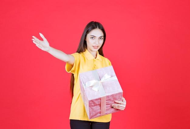 Mulher de camisa amarela segurando uma caixa de presente rosa e convidando alguém para se aproximar e levá-la.