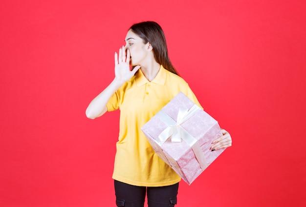Mulher de camisa amarela segurando uma caixa de presente rosa e ligando para alguém.