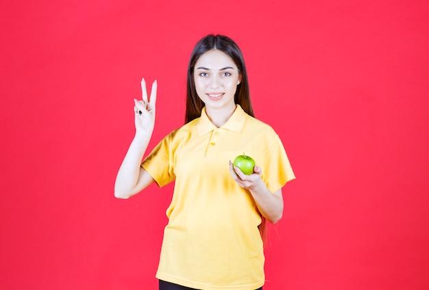 Mulher de camisa amarela segurando uma maçã verde e se sentindo satisfeita.