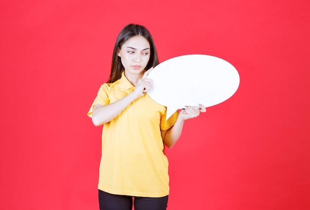 Mulher de camisa amarela segurando uma placa de informações oval e parece confusa e pensativa.