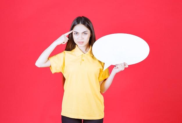 Mulher de camisa amarela, segurando uma placa de informações oval e tendo uma boa ideia.