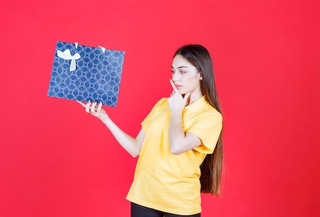 Mulher de camisa amarela segurando uma sacola de compras azul e parece confusa e pensativa.