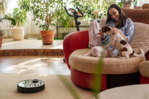 Mulher de camisa azul brinca com cachorro, raça de jack russell terrier em casa no sofá, aspirador de pó robótico no tapete