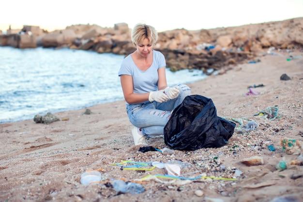 Mulher de camisa azul com luvas brancas e um grande pacote preto coletando lixo na praia. proteção ambiental e conceito de poluição do planeta