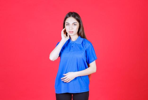 Mulher de camisa azul em pé na parede vermelha e parece confusa e pensativa.