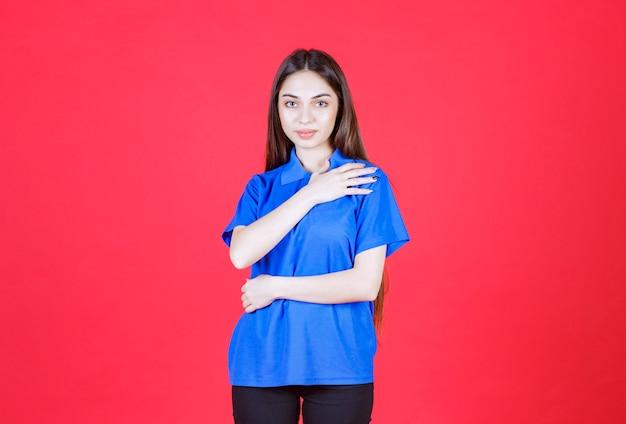 Mulher de camisa azul em pé na parede vermelha.
