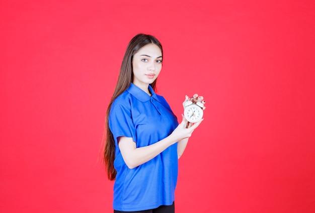 Mulher de camisa azul, segurando um despertador.