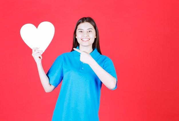 Mulher de camisa azul, segurando uma placa de informações de forma de coração.