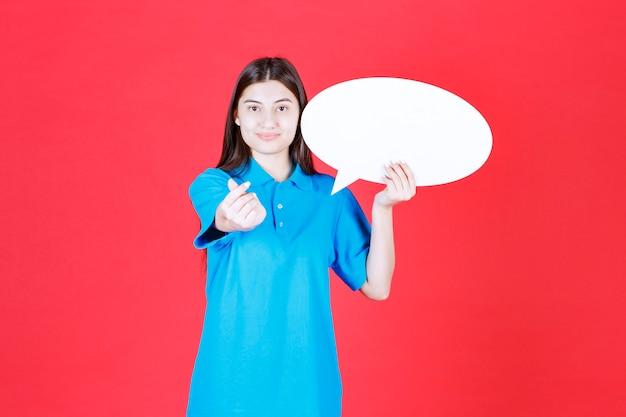 Mulher de camisa azul, segurando uma placa de informações oval e pedindo dinheiro.