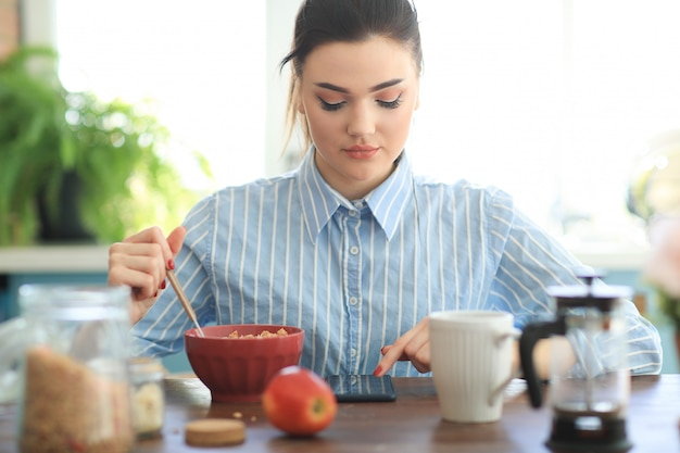 Mulher de camisa azul, tomando café da manhã e verificando seu telefone