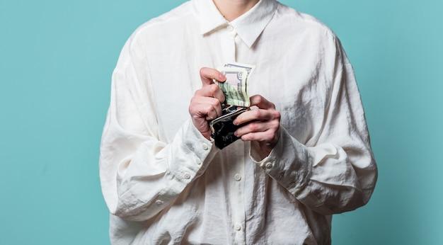 Mulher de camisa branca com dinheiro e carteira na parede azul