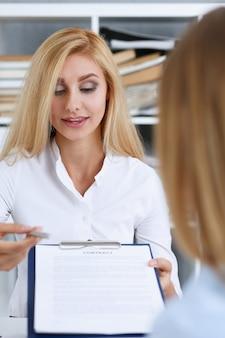 Mulher de camisa branca com forma de contrato