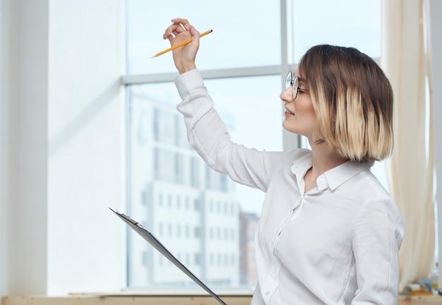 Mulher de camisa branca documentos trabalho de escritório. foto de alta qualidade