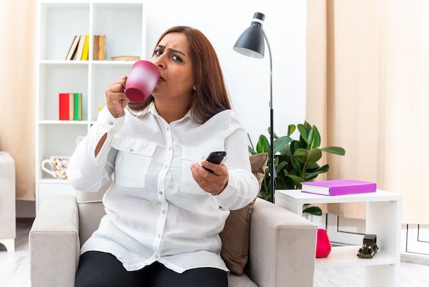 Mulher de camisa branca e calça preta assistindo tv, bebendo chá em uma xícara, sentada na cadeira na sala iluminada