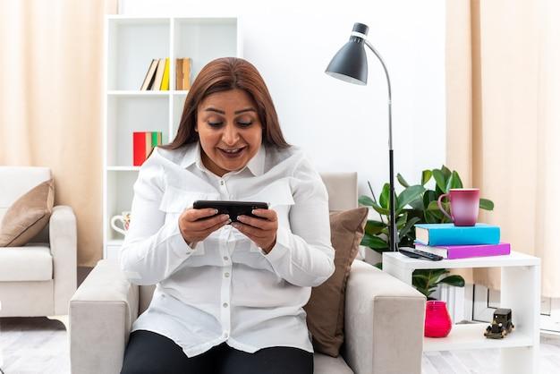 Mulher de camisa branca e calça preta jogando no smartphone feliz e animada, sentada na cadeira na sala iluminada