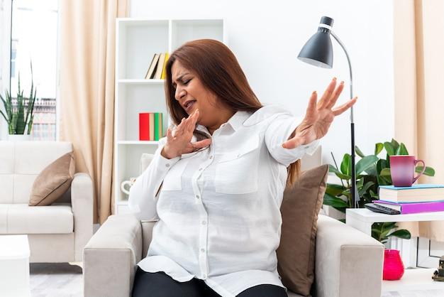 Mulher de camisa branca e calça preta olhando para o lado com expressão de nojo no rosto de mãos dadas fazendo gesto de defesa, sentada na cadeira na sala iluminada