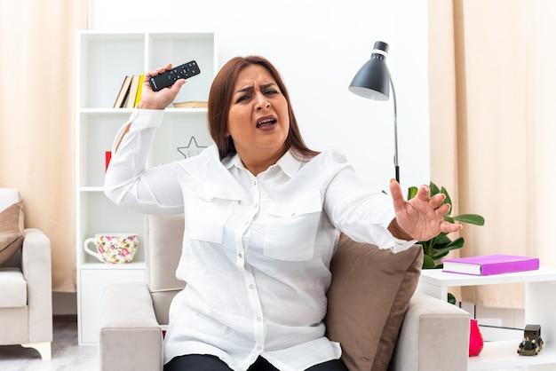 Mulher de camisa branca e calça preta segurando o controle remoto da tv com raiva e frustrada, sentada na cadeira na sala iluminada