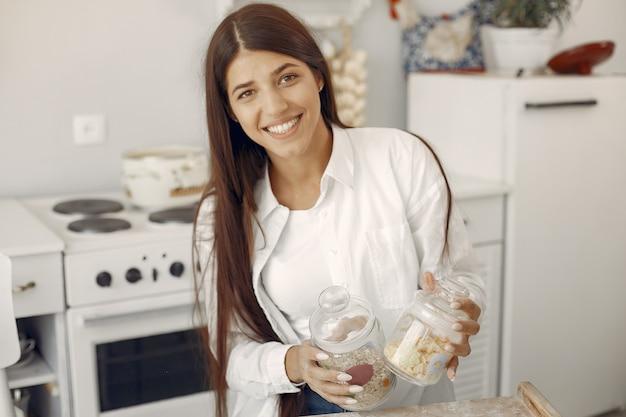 Mulher de camisa branca em pé na cozinha com aveia