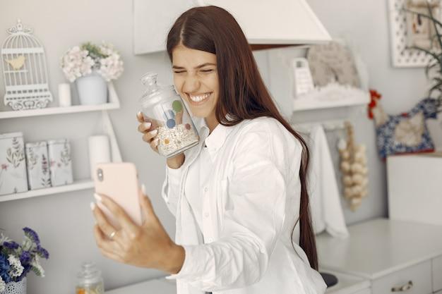 Mulher de camisa branca em pé na cozinha e fazendo uma selfie