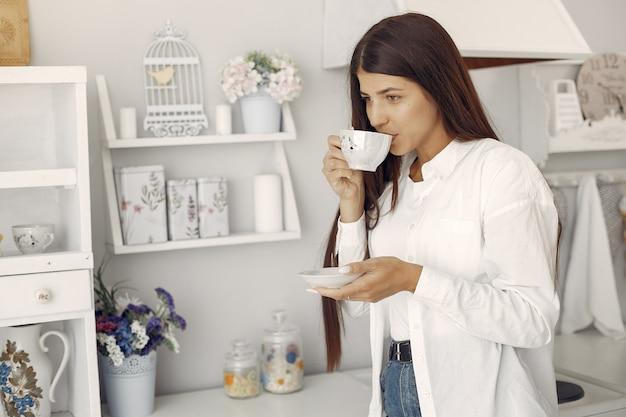 Mulher de camisa branca em pé na cozinha e tomando um café