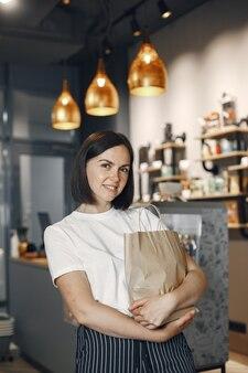 Mulher de camisa branca no supermercado. morena olha para a câmera e sorri.