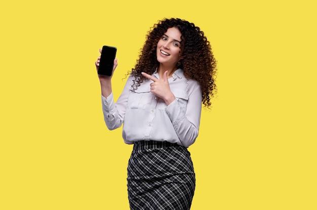 Mulher de camisa branca segura o smartphone e aponta com o dedo indicador na tela em branco. mulher de negócios sobre fundo amarelo isolado. conceito de casino online
