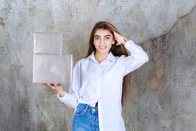 Mulher de camisa branca segurando caixas de presente de prata e se sentindo sedutora.