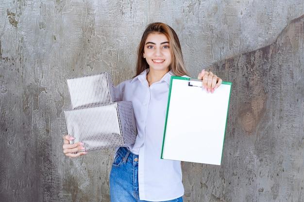 Mulher de camisa branca segurando caixas de presente prata e uma lista de assinaturas branca.