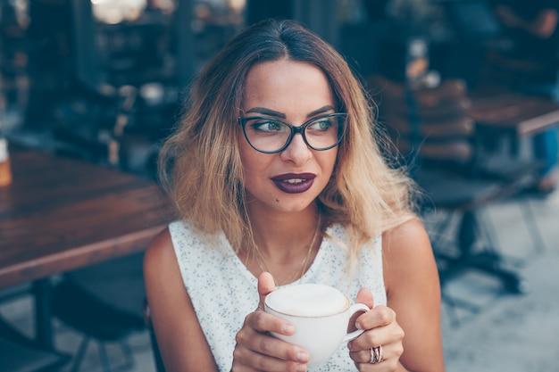 Mulher de camisa branca texturizada, sentado e segurando o café no terraço do café durante o dia
