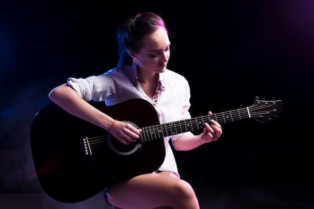 Mulher de camisa branca, tocando violão no palco