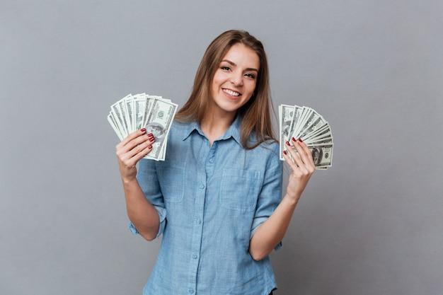 Mulher de camisa com dinheiro nas mãos