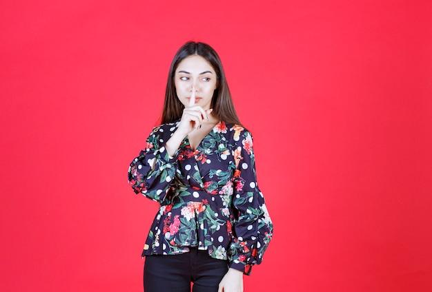 Mulher de camisa floral em pé na parede vermelha e pedindo silêncio.