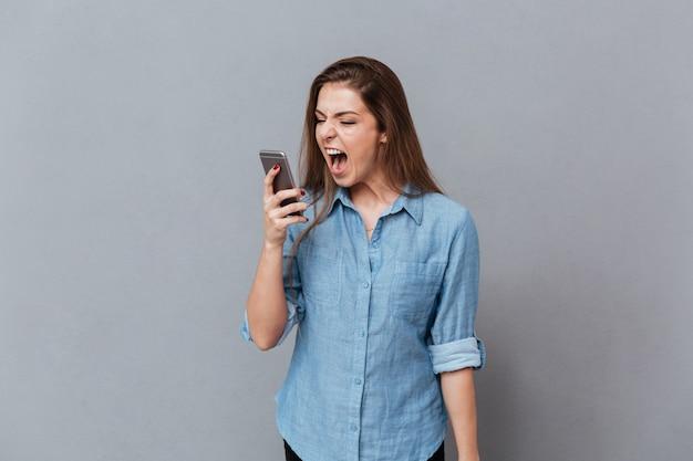Mulher de camisa, gritando no telefone