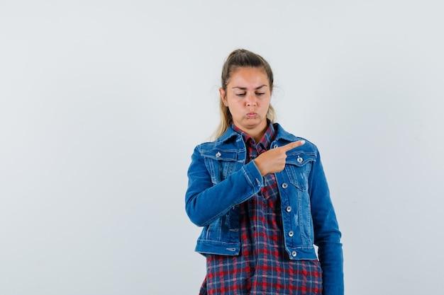 Mulher de camisa, jaqueta apontando para o lado direito e parecendo chateada, vista frontal.