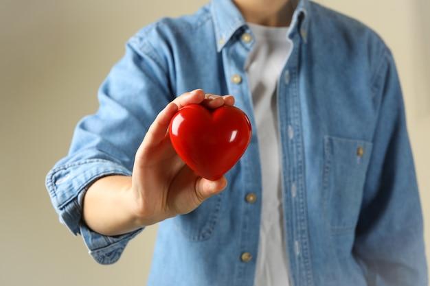 Mulher de camisa jeans segurando um coração vermelho
