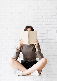 Mulher de camisa marrom sentada na cadeira com as pernas cruzadas segurando um livro aberto