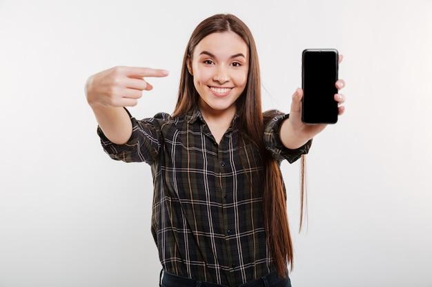 Mulher de camisa, mostrando a tela do smartphone em branco
