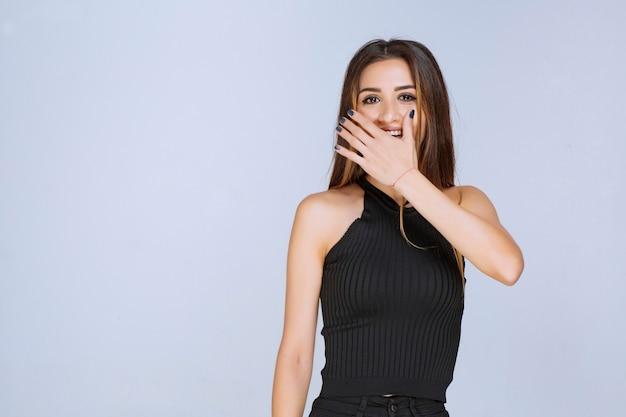 Mulher de camisa preta, cobrindo o rosto com as mãos.