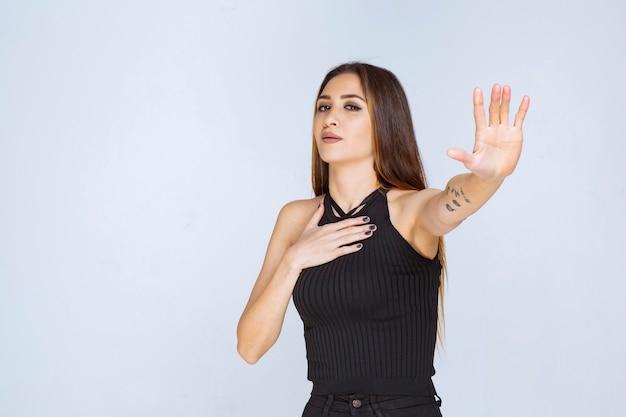 Mulher de camisa preta, fazendo sinal de pare.