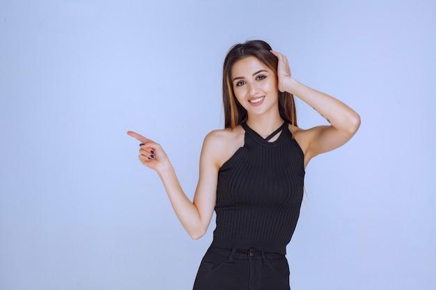 Mulher de camisa preta, mostrando algo à esquerda.