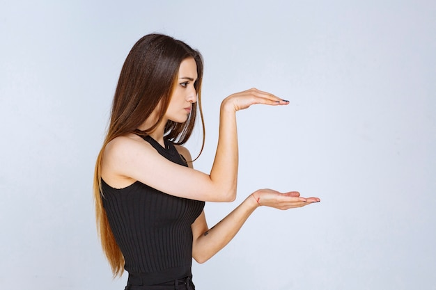 Mulher de camisa preta, mostrando as dimensões estimadas de um objeto.