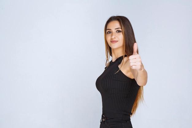 Mulher de camisa preta, mostrando o polegar para cima o sinal.